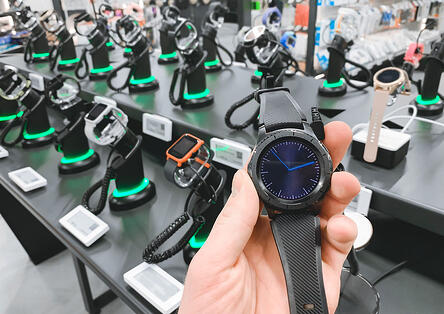 Man-in-the-electronics-store-holds a-smart-watch-in-his-hands