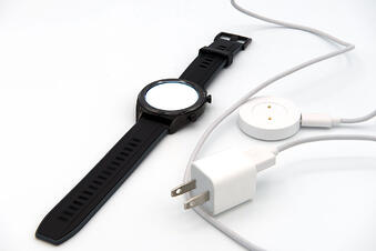Watch and battery charger separately on white background