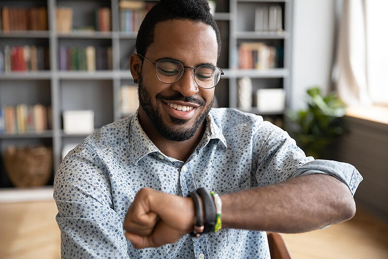 man-looking-at-smartwatch-while-at-home